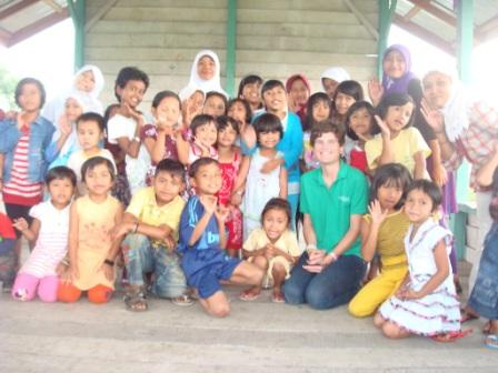 Anne Scott (in the green shirt) takes a group photo with children in the small village of Ronga Ronga in Indonesia.
