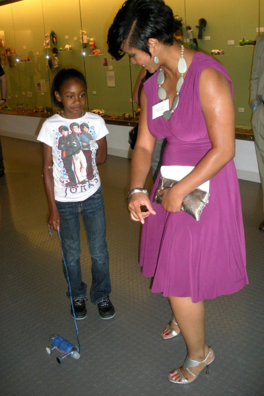 "Shauntay Hinton helps a girl with a toy at the opening of ""The Power to Play"" in Los Angeles."