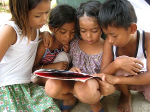 Children participate in a story-telling session in a Child Centered Space set up by ChildFund in the Philippines.