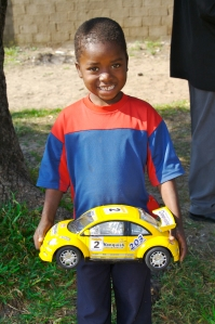 A boy in Mozambique shows off a car he likes to play with.