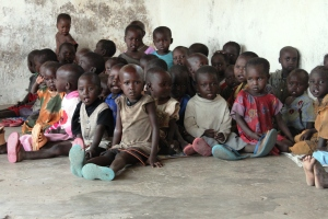 Children sit on floor waiting for food