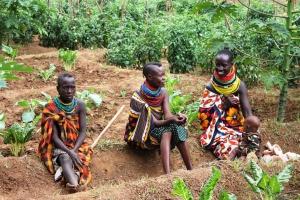 Three Kenyan women sit in garden