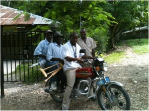 Three men on a motor bike