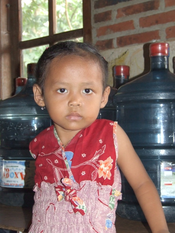 Andien, 4, likes to climb on the water jugs her mother sells.