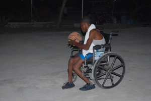 Man in wheelchair shooting basketball