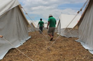 men walking among tent camp