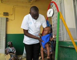 Health worker weighs child.
