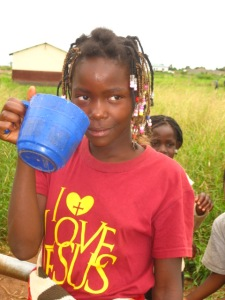 a girl drinks water from a cup