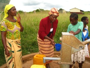 women at a water pump