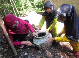 3 women installing a clay pot