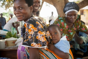 A Ugandan mother brings her child to a nutrition day in Budaka District. Photo by Jake Lyell.