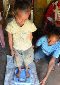 health care volunteer weighing a child
